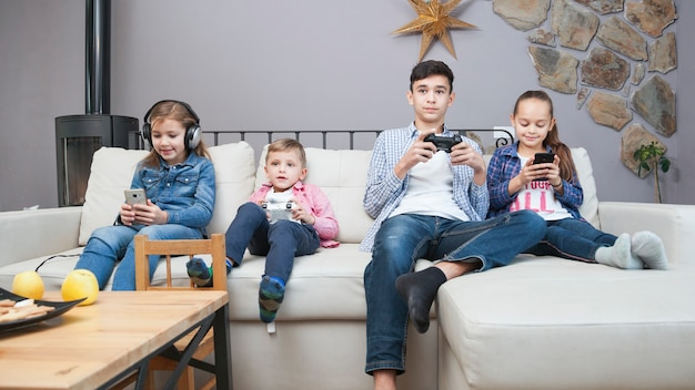 Siblings using technologies on sofa