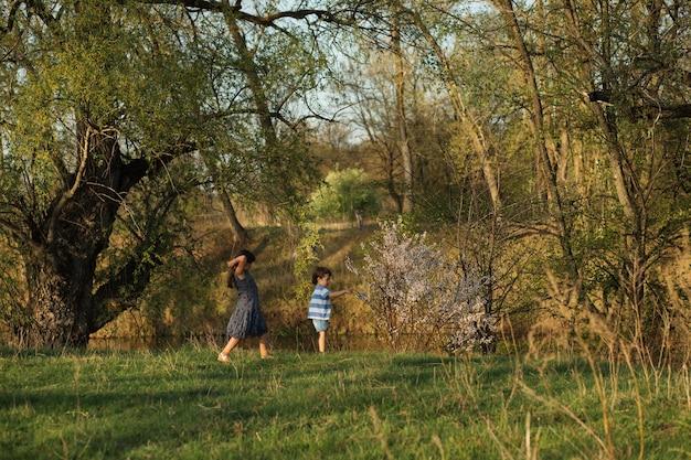 春の夕方の森を一緒に歩く兄弟。小さなかわいい白人の女の子と男の子。