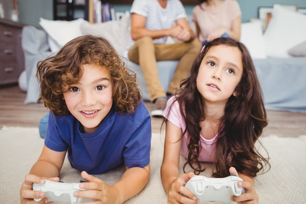 Siblings with playing video game on carpet