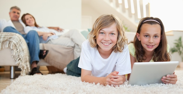 Siblings with tablet on the carpet