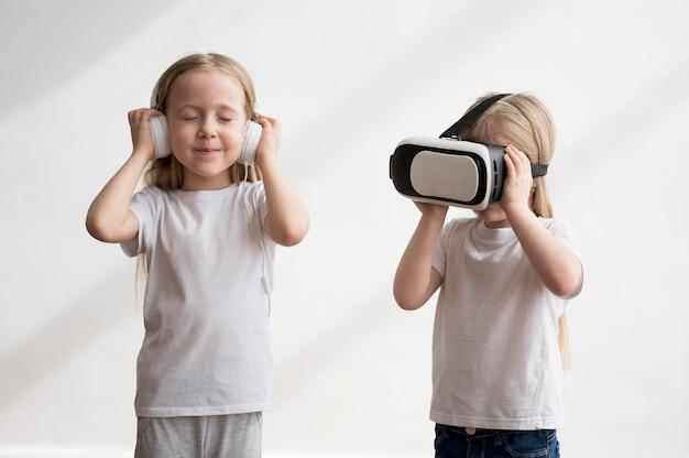 Братья и сестры с гарнитурой виртуальной реальности и наушниками