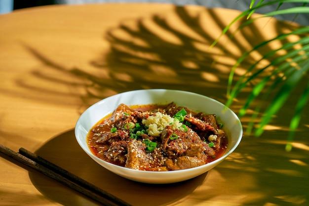 Сычуаньская острая говядина в остром соусе, чеснок, перец, кунжут в белой миске. китайская кухня. шуйчжу, шуй чжу
