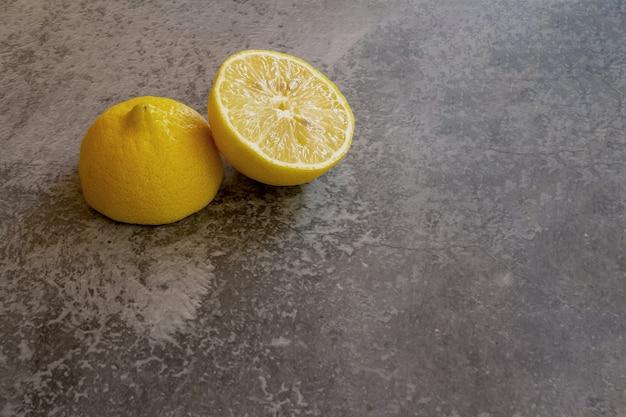 Сицилийский лимон, разрезанный пополам на обожженной цементной поверхности