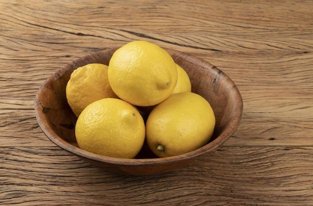 木製のテーブルの上のボウルにシチリアレモン