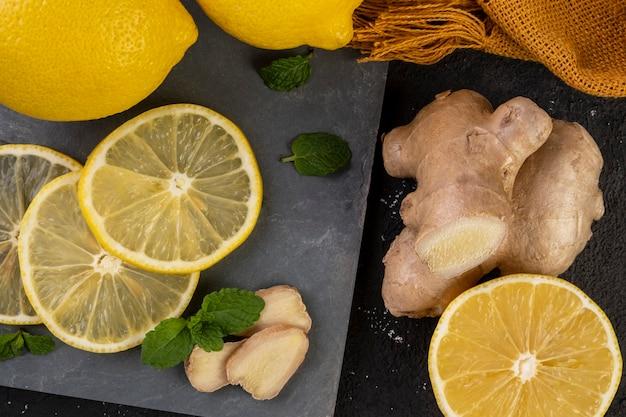 Сицилийские лимоны на сланцевом камне с листьями имбиря и мяты.