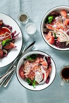 회향, 오렌지, 자몽, 라디 키오 샐러드와 블루 린넨 식탁보에 발사믹 드레싱을 곁들인 시칠리아 샐러드.