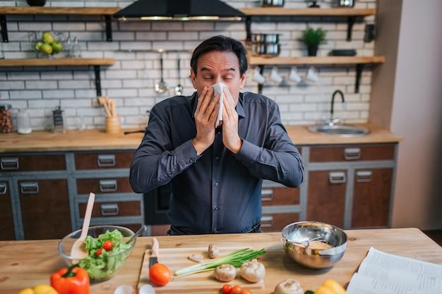 白いナプキンにくしゃみをする病気の成人男性。彼は台所のテーブルに立っています。カラフルな健康野菜とスパイスでいっぱいの机。