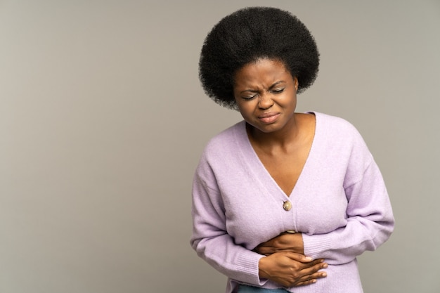 Sick african woman suffer acute period pain or ache in stomach pressing hands to abdominal belly