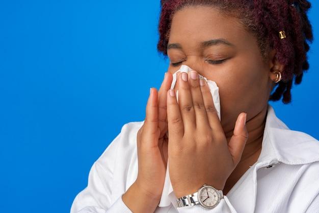 青い表面に対して紙ナプキンでくしゃみをする病気のアフロ女性