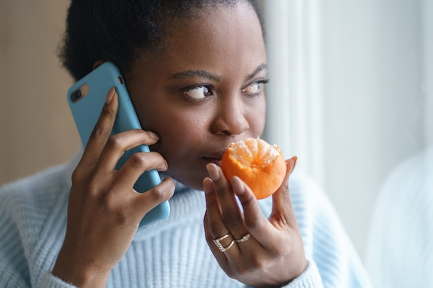 Sick afro woman trying to sense smell of half fresh tangerine talking on phone. covid-19