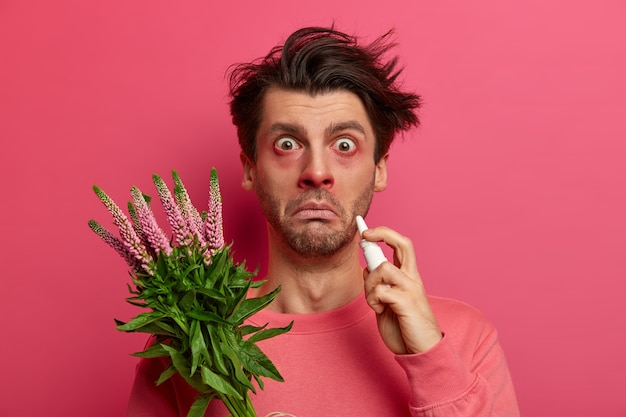 Sick allergic young man drips nose with nasal drops, has red eyes and nose, allergy on plant, symptoms of rhinitis or hay fever, stares , poses against pink wall, reacts on pollen