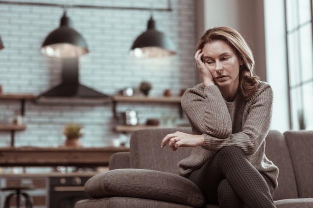 病気で落ち込んでいます。灰色のセーターを着た金髪の成熟した女性が、ひどく気分が悪く落ち込んでいる
