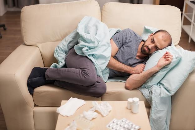 自己隔離中にソファに横たわっている病気で落ち込んでいる男性。