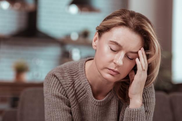 Больной и одинокий. подавленная зрелая светловолосая женщина чувствует себя больной и одинокой остается одна дома