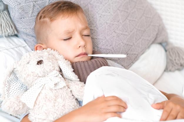 아프고 슬픈 소년은 입에 온도계를 넣고 팔에 부드러운 장난감을 들고 침대에 누워 있습니다