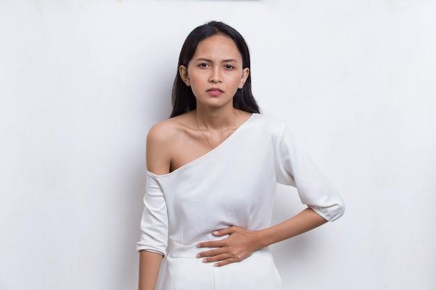 흰색 배경에 고립 된 복통을 가진 아픈 아시아 아름 다운 젊은 여자
