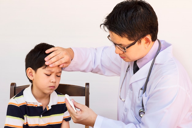흰색 배경 위에 남성 의사에 의해 검사되는 아픈 아시아 소년