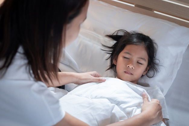 Sick asian child girl get sick and sleep on the bed, mother taking care and cover the blanket on her daughter