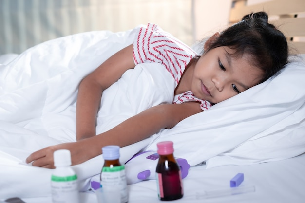 Sick asian child girl is lying on bed and looking sadly on medicine.