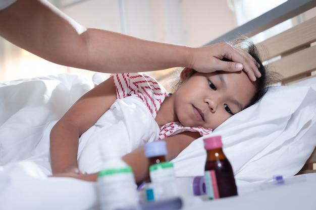 Больная азиатская девочка лежит на кровати, а ее мать заботится и трогает лоб
