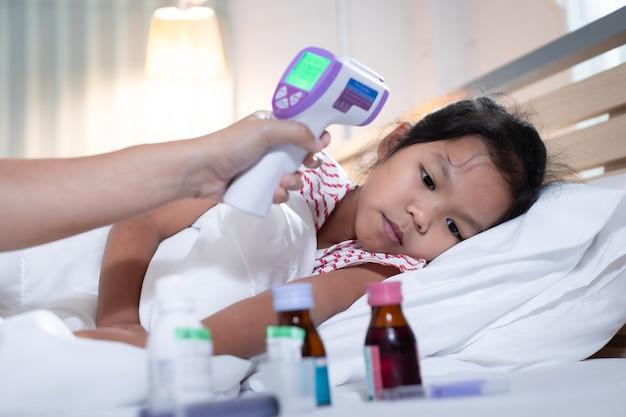Больная азиатская девочка спит на кровати, а ее мать проверяет
