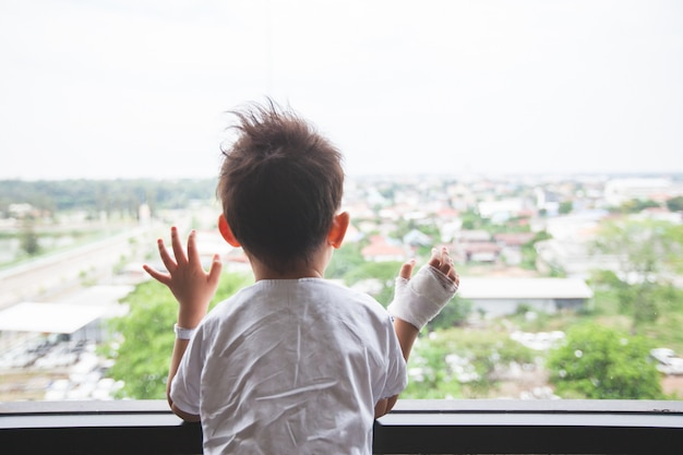 Sick asian child at the hospital looking outside through the window