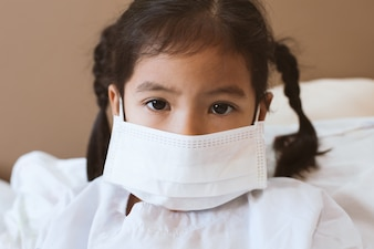 Sick asian little child girl wear protection mask while live in the hospital