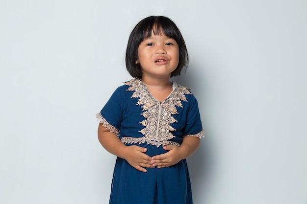 흰색 배경에 고립 된 복통을 가진 아픈 아시아 소녀