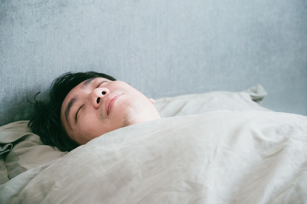Sick asian male sleeps on the bed. patient man resting from illness.