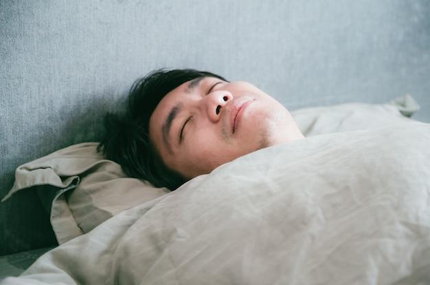 病気のアジア人男性がベッドで寝ています。病気から休んでいる患者の男性。