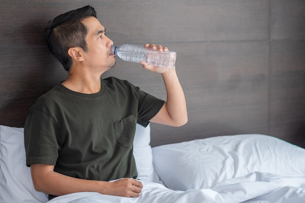 Sick asian man lies drinking on a white bed in his bedroom. for good health