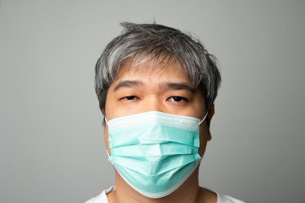 医療用フェイスマスクと肩の痛みとストレスを身に着けている病気のアジア人。保護パンデミックコロナウイルスと呼吸器疾患の概念