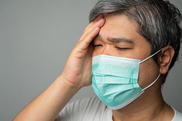 医療用フェイスマスクを着用し、頭痛を頭に抱える手を取ります。保護パンデミックコロナウイルスと呼吸器疾患の概念
