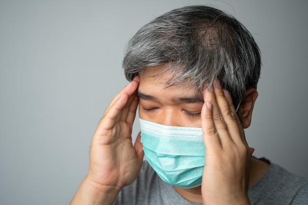医療用フェイスマスクを身に着けている病気のアジア人男性と頭の中で頭痛を保持するために手を取ります
