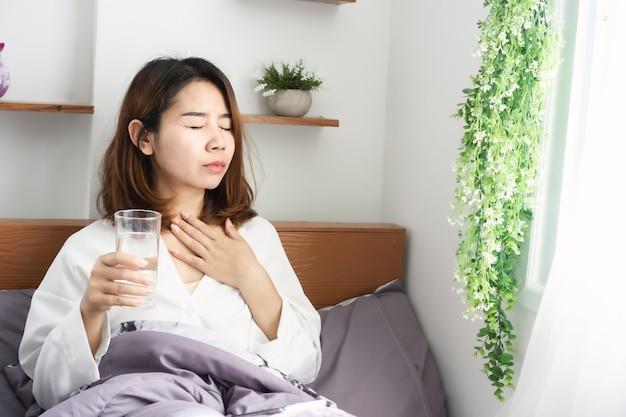 인후통으로 고통받는 아픈 아시아 여성, 침대에서 식수