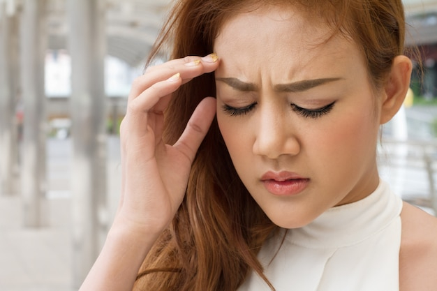 Sick asian woman suffers from headache, migraine, vertigo, dizziness