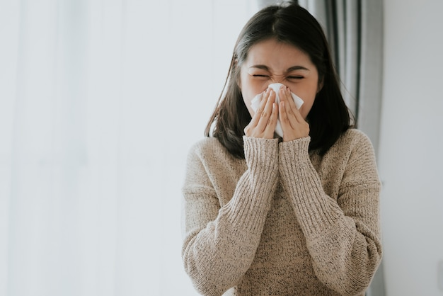 Sick asian woman using a tissue to sneeze at home