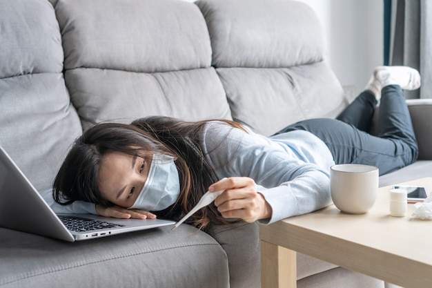 Sick asian woman wearing medical mask working on laptop from home office. sad girl with cold lying on sofa while looks at the thermometer. work from home, health problems and home isolation concept