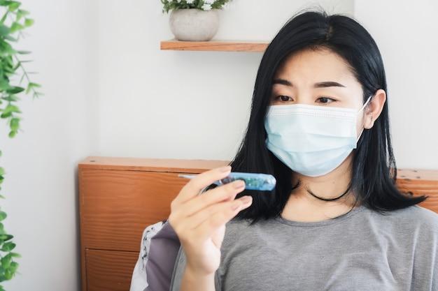 温度計を持っている保護マスクの手を持つ病気のアジアの女性