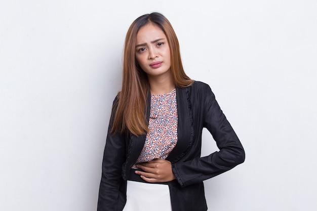 Больная азиатская молодая деловая женщина, имеющая боль в животе, изолированная на белом фоне