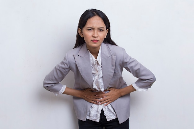 Sick asian young business woman having a stomach ache isolated on white background