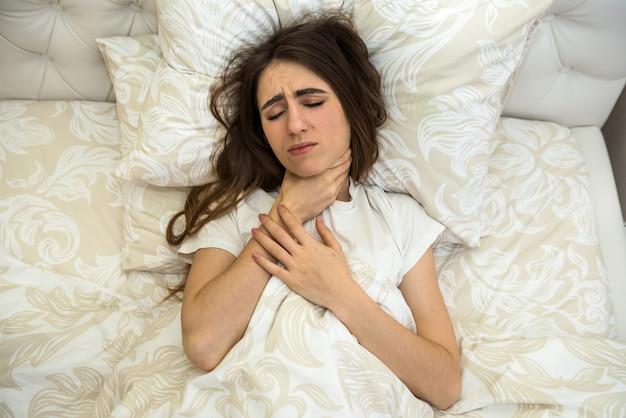 약을 복용과 침대에 누워 아픈 매력적인 여자. 코로나 바이러스.