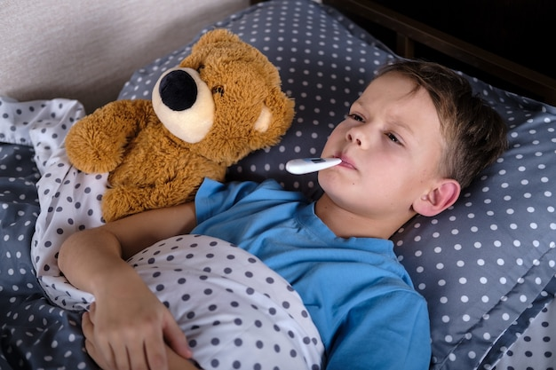 Больной мальчик лежал в постели с термометром во рту рядом с игрушкой