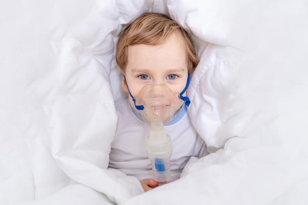 Больной мальчик с ингалятором лечит горло дома, концепция здоровья и ингаляционное лечение