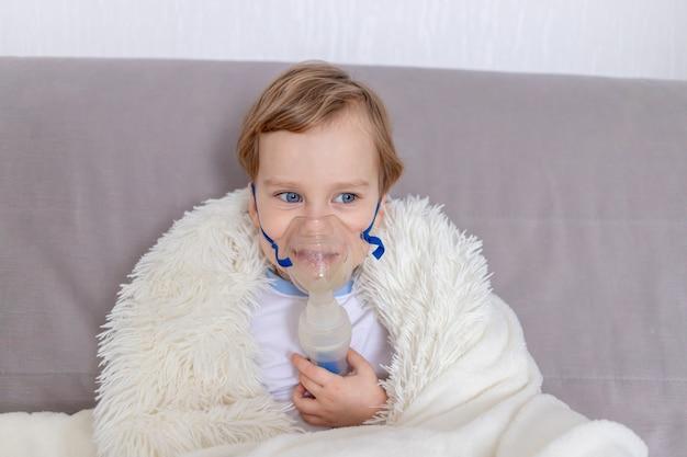 Больной мальчик с ингалятором лечит горло дома концепция здоровья и ингаляционного лечения