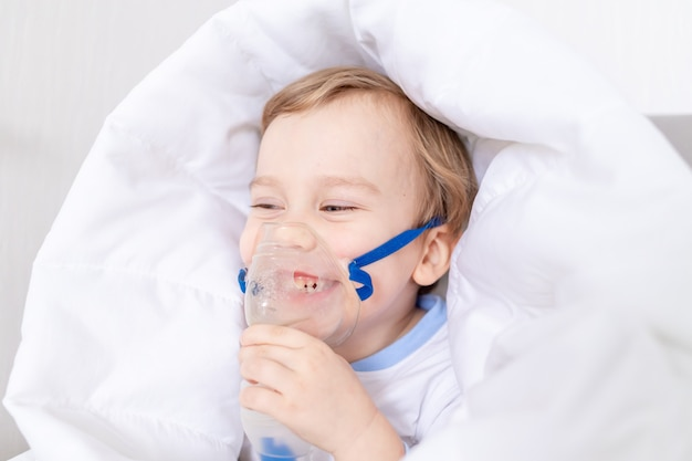 Sick baby boy with inhaler treats throat at home, the concept of health and inhalation treatment