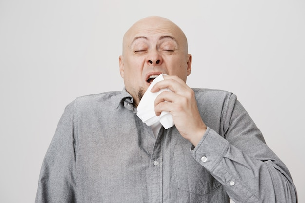 Sick bald middle-aged guy sneezing in napkin
