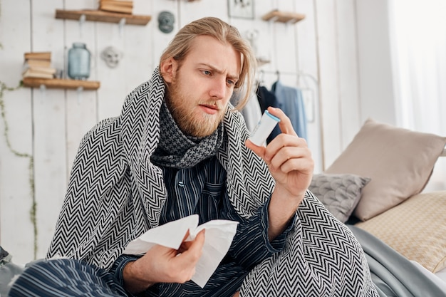 Sick bearded fair-haired man in sleepwear sits on bed surrounded by blanket and pillows, frowns while reading prescription on pills, holds handkerchief in hand. health problems, bad cold and flu.