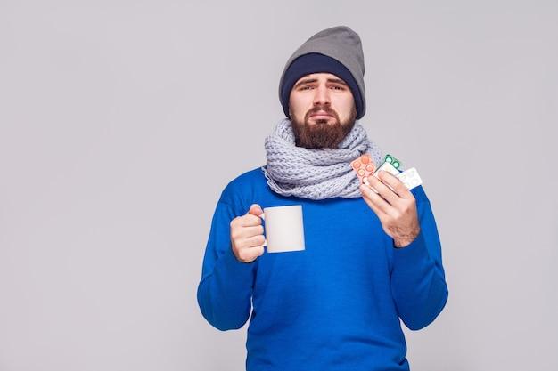 お茶、多くの錠剤とカップを保持している病気のひげを生やした男。スタジオショット、灰色の背景に分離
