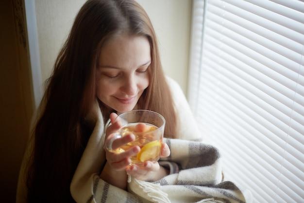 Больная красивая женщина с простудой и пьет горячий чай с лимоном, сидя у окна в загородном доме зимой